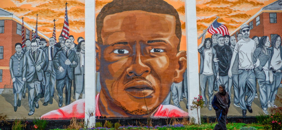 A man, who declined to offer his name, walks past a mural of Freddie Gray in the Sandtown-Winchester neighborhood of Baltimore, December 17, 2015. On Wednesday, Judge Barry Williams declared a mistrial in the case of Police Officer William Porter, one of six officer charged connection with the death of Freddie Gray. REUTERS/Bryan Woolston EDITORIAL USE ONLY. NO RESALES. NO ARCHIVE - RTX1Z4YV